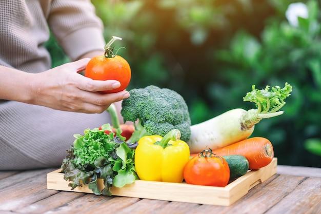 Een vrouw die verse gemengde groenten vasthoudt en plukt van een houten dienblad op tafel