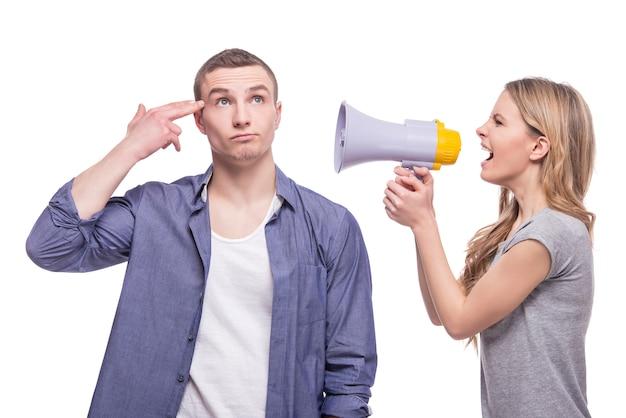 Een vrouw die via een megafoon tegen een man schreeuwt.