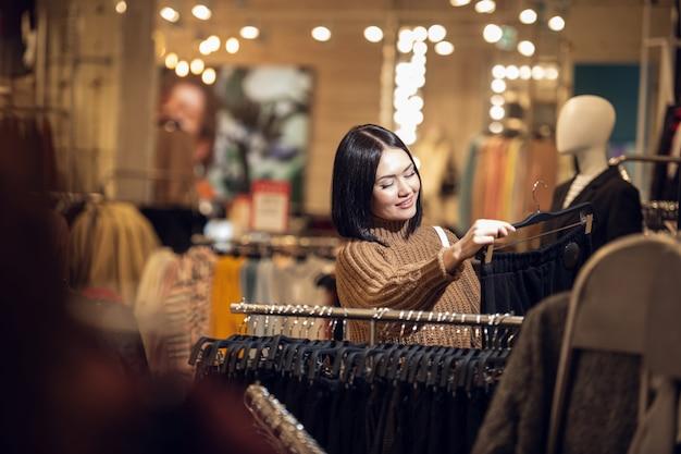 Een vrouw die voor kleren winkelt.