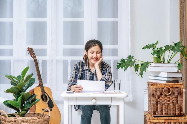 Een vrouw die vrolijk aan het bureau zit, analyseert documenten.