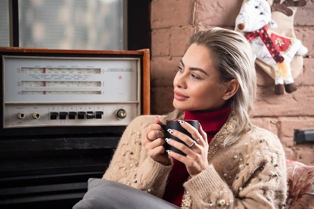 Een vrouw die wegkijkt en koffie drinkt