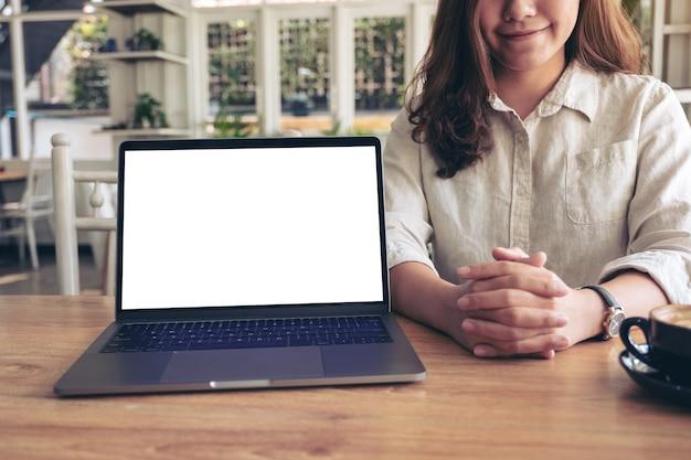 Een vrouw die werk met laptop met leeg wit scherm op houten lijst voorstelt