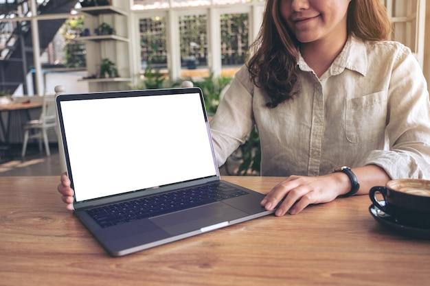 Een vrouw die werk met laptop presenteert met een leeg wit scherm op houten tafel terwijl ze koffie drinkt