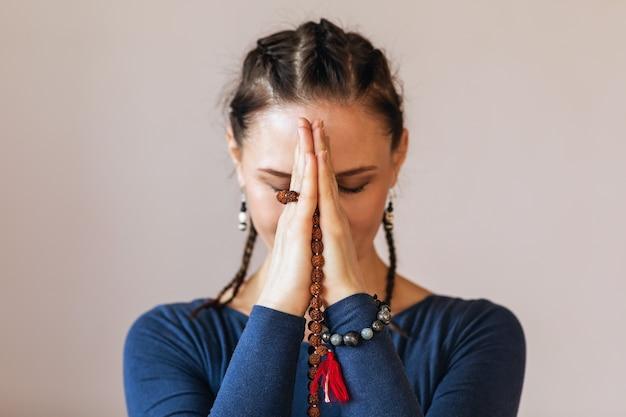 Een vrouw die yoga beoefent, voert meditatie uit met namaste dichtbij haar gezicht met een rozenkrans in haar handen