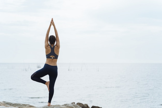 Een vrouw die yogahoudingen op het strand uitoefent
