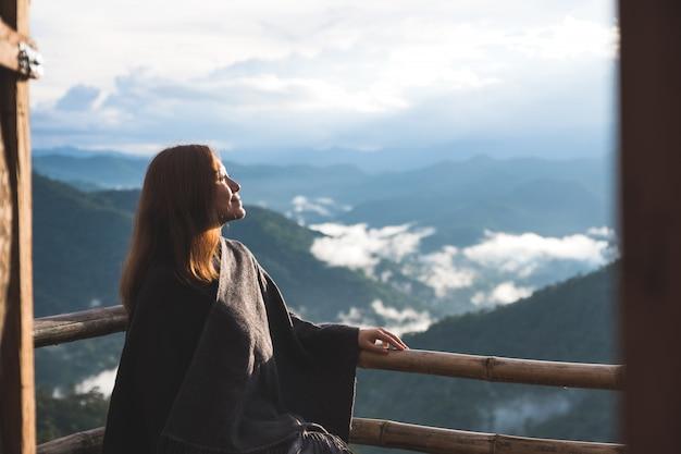 Een vrouw die zich alleen op balkon bevindt dat bergen op mistige dag met blauwe hemel in de ochtend bekijkt