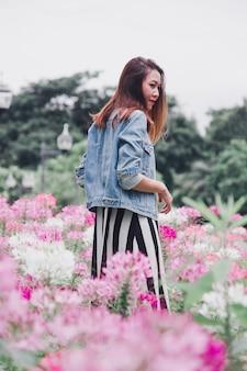 Een vrouw die zich in een roze bloementuin bevindt