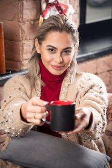 Een vrouw die zit en koffie aanbiedt