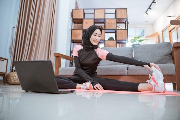 Een vrouw draagt een hijab-gymkleding wanneer ze zit, strekt zich uit met één been opzij en wordt met één hand vastgehouden wanneer ze voor een laptop in huis zit
