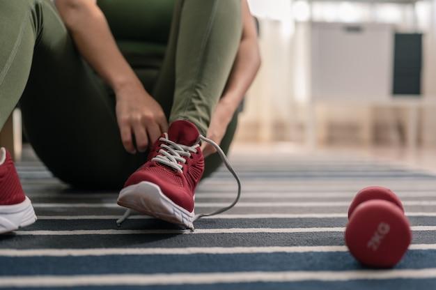 Een vrouw draagt schoenen om in haar huis te sporten binnen sporten tijdens quarantaine thuis sporten