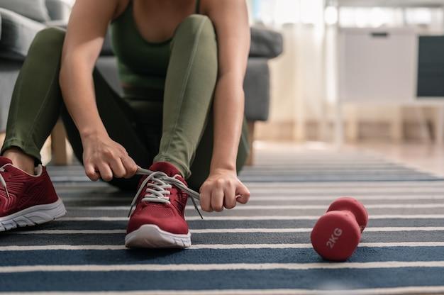 Een vrouw draagt schoenen om in haar huis te sporten binnenshuis sporten tijdens quarantaine oefening