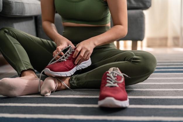 Een vrouw draagt schoenen om in haar huis te sporten binnenshuis sporten tijdens quarantaine