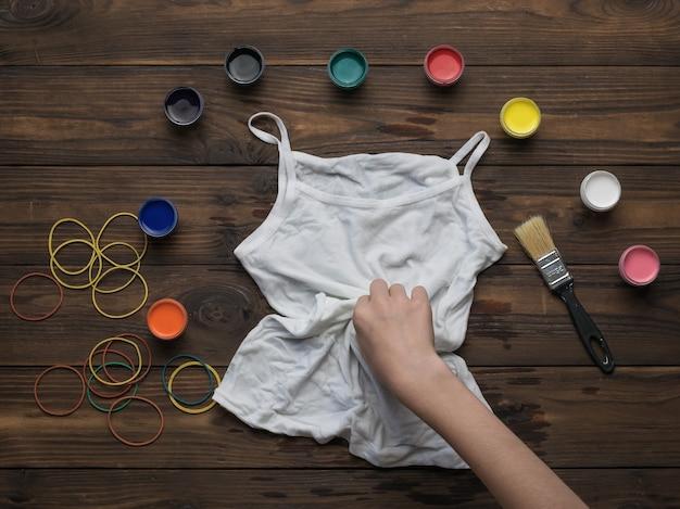 Een vrouw draait een wit t-shirt om in te kleuren in de stijl van tie-dye. stof beitsen in tie-dye-stijl.