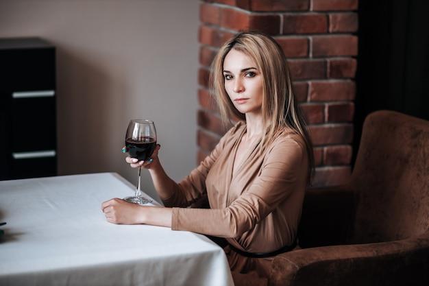 Een vrouw drinkt rode wijn in een restaurant