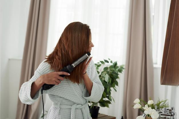 Een vrouw droogt haar haar met een föhn in de badkamer en kijkt in de spiegel. mooie dame doet haar haar thuis.