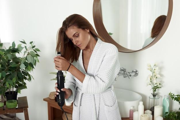 Een vrouw droogt haar haar met een föhn in de badkamer. mooie dame doet haar haar thuis