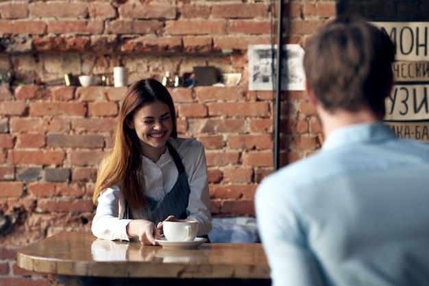 Een vrouw, een ober, neemt een bestelling aan van een man in een café