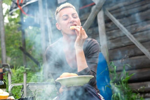 Een vrouw eet sjasliek, in het dorp. voor elk doel.