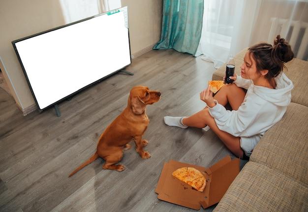 Een vrouw eet thuis pizza, kijkt tv en een cocker-spaniëlhond bedelt