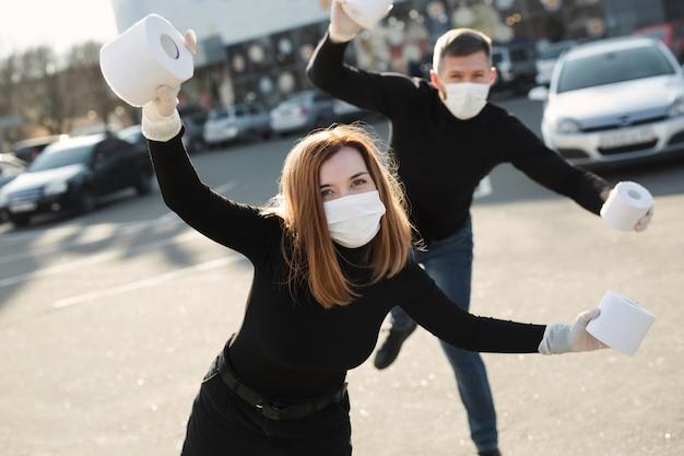 Een vrouw en een man in een coronavirus gezichtsmasker houden grote rollen wc-papier vast in een straat in de stad en genieten