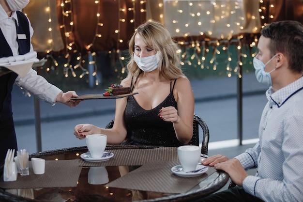 Een vrouw en een man in medische beschermende maskers aan een tafel in een café