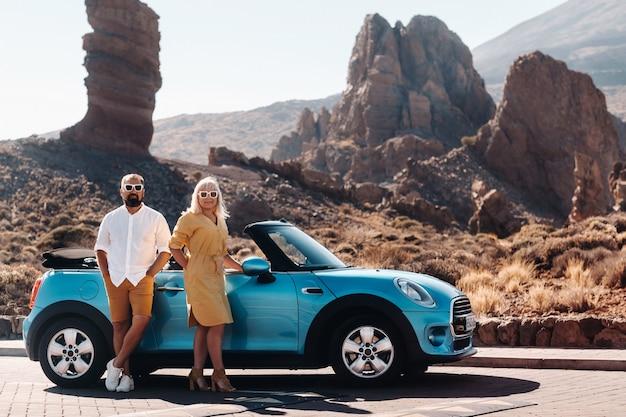 Een vrouw en een man met een bril in een cabriolet op een reis naar het eiland tenerife. de krater van de teide-vulkaan, canarische eilanden, spanje.
