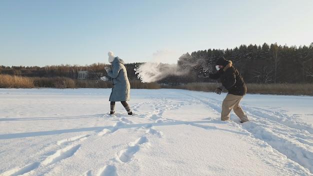 Een vrouw en een man met medische maskers spelen sneeuwballen in een winterpark, het dragen van een medisch masker op openbare plaatsen helpt de ontwikkeling van de coronavirus-epidemie te voorkomen