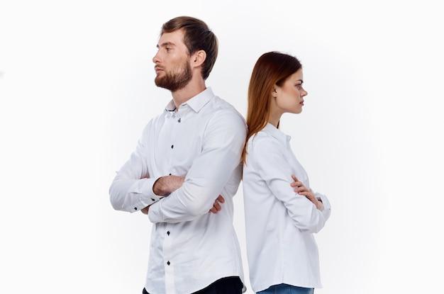 Een vrouw en een man staan met hun rug naar elkaar toe op een lichte achtergrond medewerkersvrienden