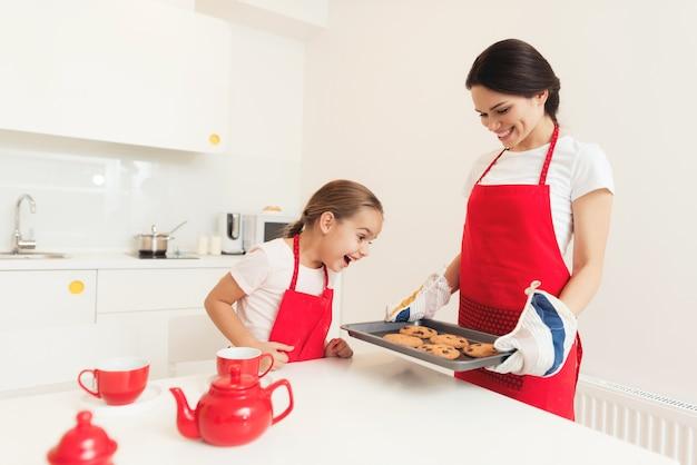 Een vrouw en een meisje in rode schorten bakken koekjes en muffins