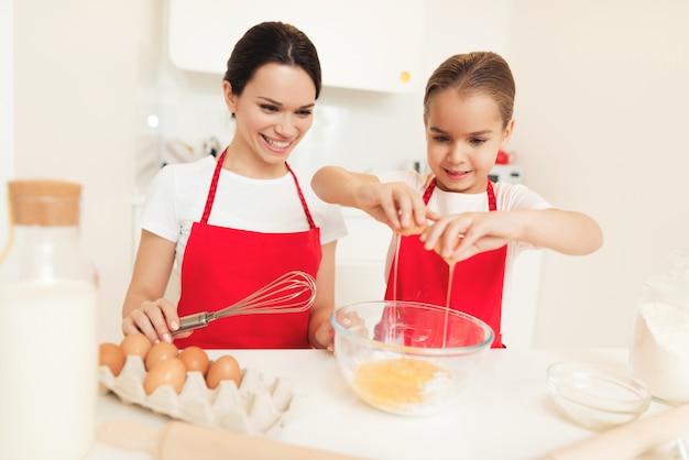 Een vrouw en een meisje in rode schorten bakken koekjes en muffins.