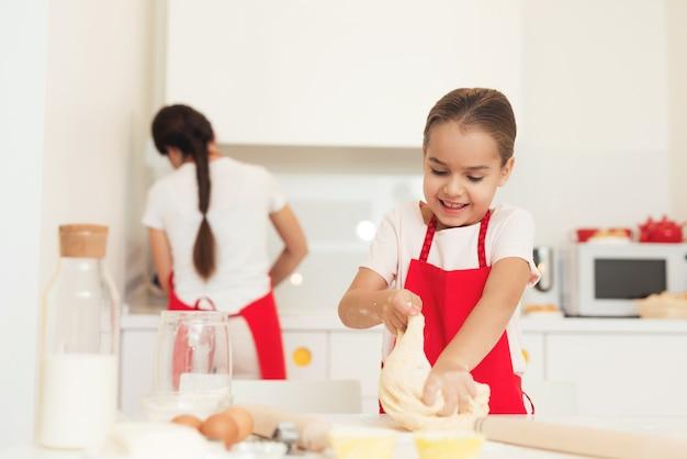 Een vrouw en een meisje in rode schorten bakken koekjes