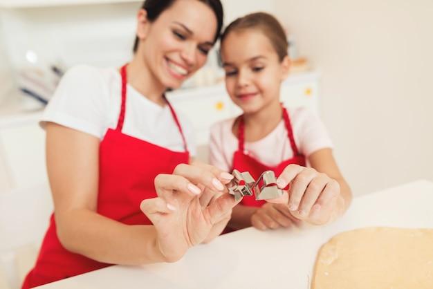 Een vrouw en een meisje in rode schorten koken samen