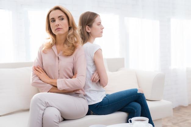 Een vrouw en een meisje zitten rug aan rug op de bank.