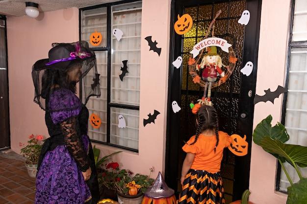 Een vrouw en een vermomd meisje gaan op de deur kloppen van een huis met halloweenversiering