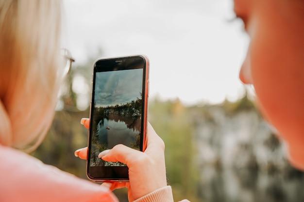 Een vrouw fotografeert op haar telefoon een kloof in het bergpark ruskeala