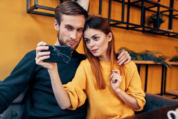 Een vrouw fotografeert zichzelf en een jonge man aan een tafel in een café-restaurant, een verliefd koppel