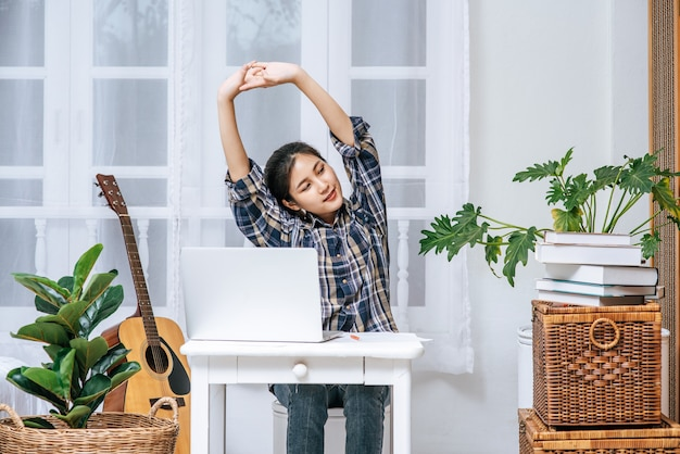 Een vrouw gebruikt een laptop op het werk en strekt haar armen uit om te ontspannen.