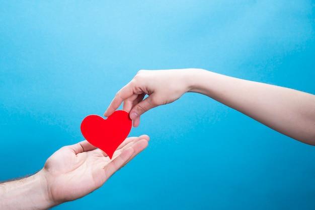 Een vrouw geeft een rood papieren hart door aan een man op een blauwe achtergrond