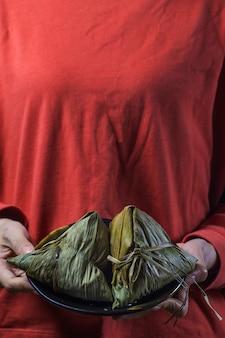 Een vrouw geeft zongzi (rijstbol) aan anderen als cadeau op dragon boat festival,