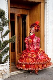 Een vrouw gekleed voor carnaval en met een gezichtsmasker