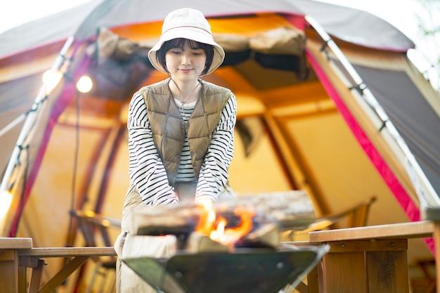 Een vrouw geniet van een kampvuur voor de tent