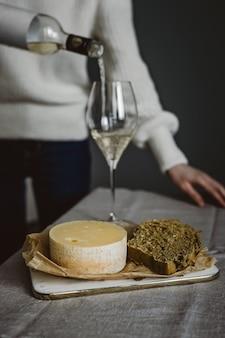 Een vrouw gieten een glas witte wijn uit een fles, kaas en brood op een snijplank. verticale levensstijlfoto