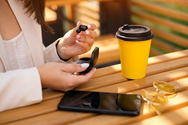 Een vrouw haalt een draadloze bluetooth-koptelefoon uit een oplaadcassette