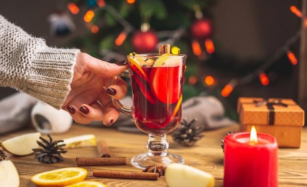 Een vrouw hand in een warme trui houdt een kopje aromatische hete glühwein tegen de kerstboom