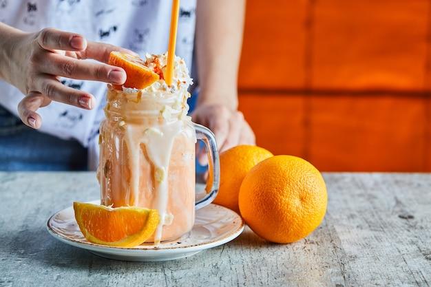 Een vrouw hand met een schijfje sinaasappel en witte plaat met sinaasappel smoothie