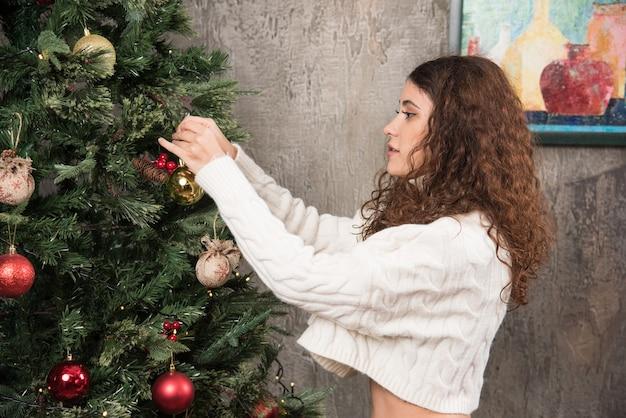 Een vrouw hangt een kerstboomspeelgoed aan een tak van een dennenboom