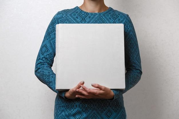 Een vrouw heeft een familiefotoboek de persoon bekijkt het fotoboekvoorbeeld beige fotoalbum trouwfotoalbum met stoffen omslag. vrouwelijke handen met vierkante fotoalbum.