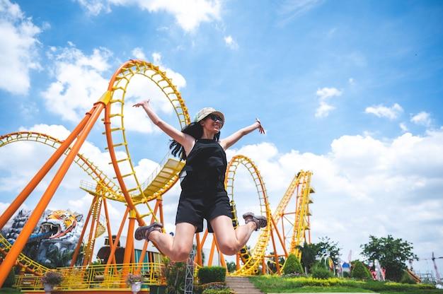 Een vrouw heeft een leuke vrolijke vreugdedag in het pretpark in zonnige zomerdag, achtbaan, springend meisje, vakantie vrijetijdsvakantie, activiteitenconcept. aziatische vrouwen, mooie heldere blauwe lucht. geniet van moment
