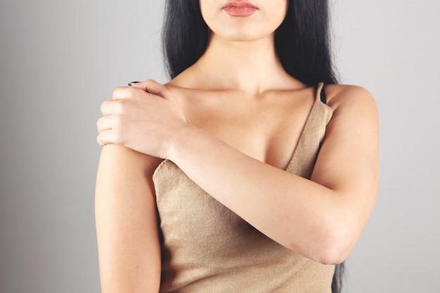 Een vrouw heeft een pijnlijke schouder op een grijze achtergrond