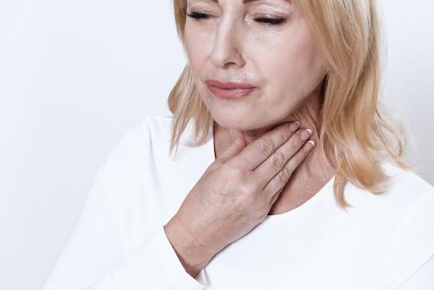 Een vrouw heeft een zere keel. ze heeft geen stem